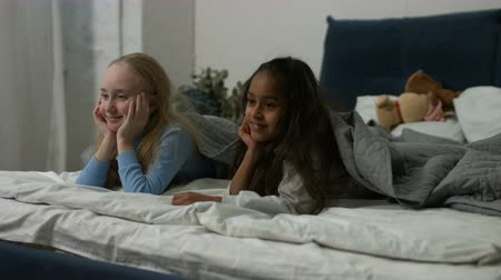 yatarken : Joyful multiracial preteen girls looking out under the blanket in bedroom and smiling. Portrait of excited little diversity girl friends having fun in the bed and posing with toothy smiles at home.