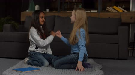 sulk : Little multiracial elementary girlfriends reconciling after quarrel and promise to be best friends forever in home interior. Cute girls hook each others fingers meaning to reconcile friendship at home