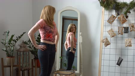 slapping : Charming smiling redhead adult woman admiring her body shape after weight loss while standing in front of mirror at home. Reflection in the mirror of cheerful female in old jeans after successful diet