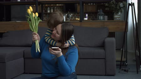 pozdrav : Cheerful preschool boy giving yellow tulips flowers to his happy mother , emabracing her from behind and kissing with love and tenderness on Mothers Day. Little son greeting his smiling mom at home. Dostupné videozáznamy