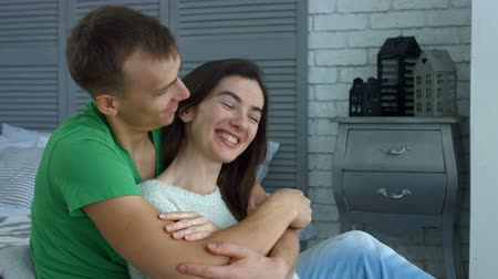 from behind : Affectionate handsome man embracing smiling woman from behind and chatting while sitting on the floor in domestic room. Attractive millennial couple in love embrace spending leisure at home.