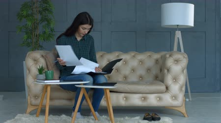 custo : Concentrated young charming woman managing her finances , calculating bills and making notes while sitting on sofa in domestic room. Busy female reviewing bank accounts using calculator at home.