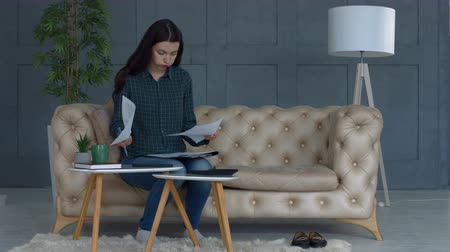 payment : Stressed young attractive woman doing her finances using calculator while sitting on sofa in domestic interior. Worried female hipster reviewing and calculating bills at home. Stock Footage