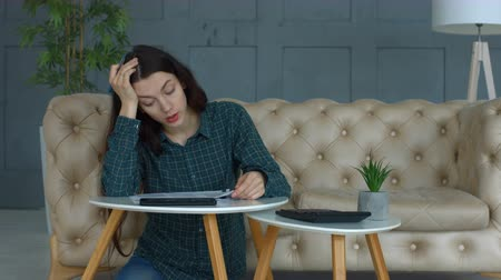 számla : Stressed beautiful long brown hair woman counting bills and expenses while doing domestic accounting in living room. Worried young woman with many debts managing her finances at home.
