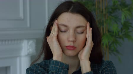 dor de cabeça : Portrait of beautiful tired woman massaging her temples to relieve headache in domestic room. Charming female freelancer having a migraine , massaging her temples to forget about constant headaches. Stock Footage