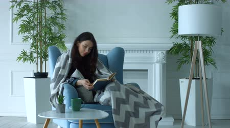 ciltli : Intelligent young woman wrapped in warm blanket reading a book in cozy armchair while spending pastime in loft apartment. Joyful relaxed woman with paper book resting in armchair at home.