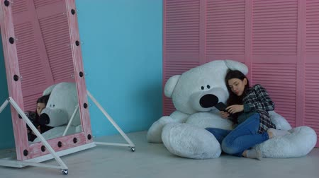 peluş : Attractive pregnant woman browsing websites with digital tablet and choosing decorating ideas for kids room while lying on big plush toy. Pregnant girl surfing the net on tablet pc in childs room. Stok Video