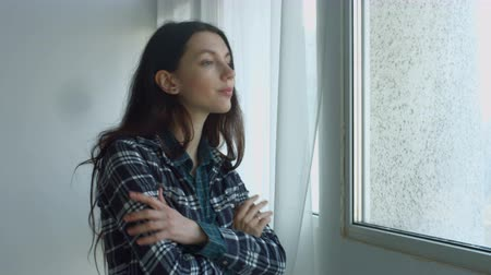 сложены : Sensual attractive long brown hair woman with folded hands looking out the window in domestic room. Young thoughtful female in plaid shirt enjoying view while standing near big window at home. Стоковые видеозаписи