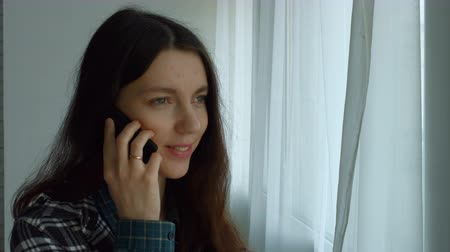 tárcsázás : Beautiful hipster woman dialing number on smart phone and talking with friends while standing near big window in domestic interior. Charming young female calling on mobile phone and chatting at home.