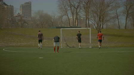 athletes foot : Young cheerful guys in sportswear playing soccer on the sports field on sunny spring day. Positive teenagers playing and kicking soccer ball during football training. Steadicam stabilized shot.