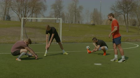 jogador de futebol : Young casual teenagers doing training session and warms up exercises on the sports field before football match. Football team warming up. Stretching - flexibility exercises for youth soccer players. Stock Footage