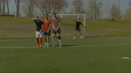 вратарь : Goalkeeper leading teammates to form wall trying to block a soccer ball during free kick on football match. Football players in wall waiting the opponent to shoot free kick.
