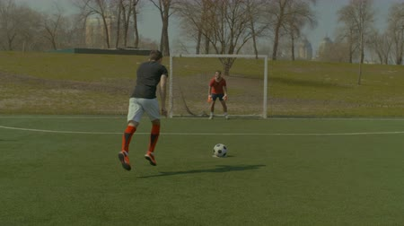 penas : Young footballer placing a soccer ball on penalty mark and shooting on goal during football match on sports green field. Soccer player taking a penalty kick during football match. Stabilized shot. Stock Footage
