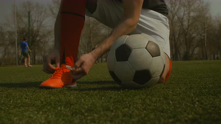 cipőfűző : Young male soccer player tying shoelace on football pitch against teammates doing football training background. Closeup. Footballer tying his shoe and kicking soccer ball on sports field. Low section.