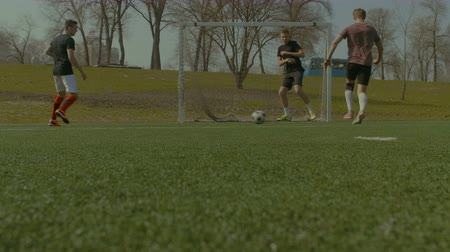 tekmeleme : Football team attacking opponent goal , passing soccer ball and striker scoring a goal during football training session on the pitch. Low angle view, Soccer forward player scoring a goal during game. Stok Video