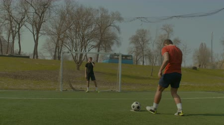 striker : Young footballer taking penalty kick and scoring a goal during football training on the pitch. Soccer player shooting soccer ball on goal while taking a penalty kick on football pitch during training.