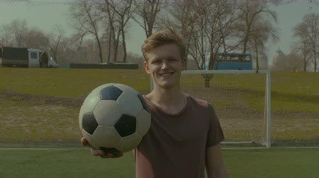 cíle : Attractive young soccer player holding soccer ball and smiling while standing on football pitch. Handsome cheerful hipster teenager in sportswear with soccer ball posing on football field.