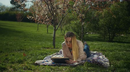 ciltli : Charming blonde young woman enjoying leisure in blooming spring park reading a book while lying on blanket on park lawn. Intelligent female student studying with book in spring park. Slow motion.