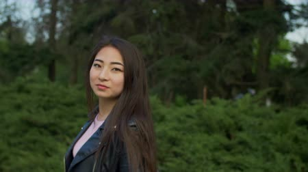femininity : Portrait of charming young asian woman with amazing straight long brown hair turning back and smiling while taking a walk in spring park. Joyful hipster girl flirting and smiling brightly outdoors.