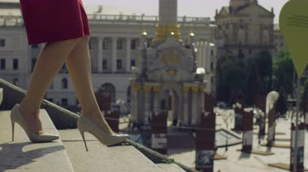 confiança : Perfect slim female legs in trendy high heel shoes stepping down on stairway in the city on sunny day over amazing urbanscape bacground. Elegant woman in high heels walking down staircase. Close-up.