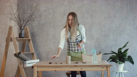 zástěra : Lovely female florist taking out from toolbox and arranging floristic tools and accessories on the table at workplace. Smiling florist putting floristic tools and equipment on table at florist shop. Dostupné videozáznamy