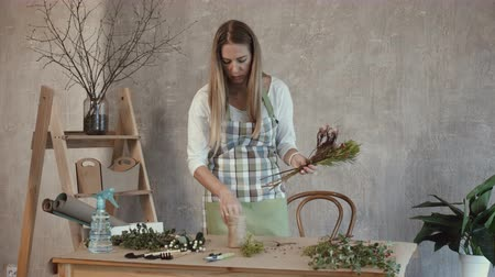 arranging : Pretty long blonde hair woman in apron creating fashion modern bouquet of different flowers and decorative plants in florist shop. Charming florist making flower bouquet at workplace.