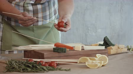 cheese types : Midsection of cooking woman pinning slices of assorted types of cheese and cherry tomatoes on wooden skewers in the kitchen while creating edible bouquet arrangement for a gift. Stock Footage