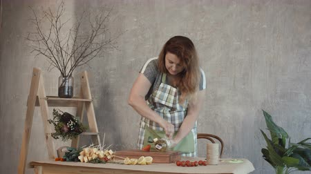 cheese types : Attractive redhead woman in apron collecting cheese and wine edible bouquet at workplace. Concentrated female making edible arrangement with assorted types of cheese and bottle of white wine.