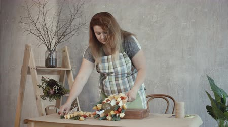 cheese types : Redhead woman in apron collecting delicious edible arrangement at workplace. Concentrated attractive female arranging food ingredients to make tasty cheese and wine arrangement at workshop.