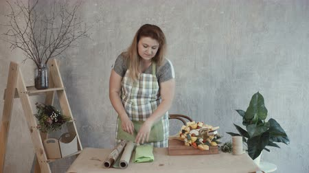 cheese types : Attractive woman in apron choosing wrapping paper for edible bouquet arrangement at workplace. Creative positive redhead female making edible arrangement and choosing kraft paper.