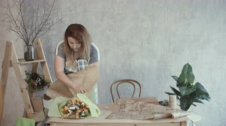 cheese types : Lovely redhead woman packing edible bouquet arrangement in wrapping paper at workplace. Positive attractive female wrapping edible bouquet composition in wrapping paper. Stock Footage