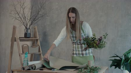 wrapping paper : Positive attractive female florist in apron wrapping flower bouquet arrangement in wrapping paper at flower shop. Professional florist creating beautiful floral composition at her workplace. Stock Footage