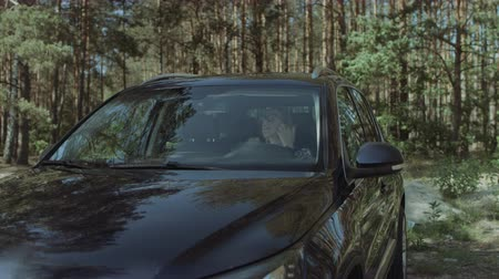 přezka : Stunning long blonde hair woman in eyeglasses getting into parked car on roadside and buckles up before driving over beautiful woodland background.