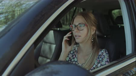 dişlek gülümseme : Cheerful blonde female driver in eyeglasses chatting on mobile phone while sitting in the car during business trip. Smiling attractive businesswoman communicating with business partners on smart phone Stok Video