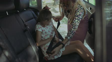 osm : Beautiful caring mother fastening cute elementary age girl with safety seat belt in the back seat of the car while family going on summer vacation road trip. Child buckles up in auto during journey. Dostupné videozáznamy