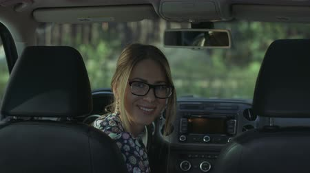 auto parking : Portrait of beautiful smiling woman in stylish eyeglasses sitting in car. Charming attractive female driver with glad positive expression sitting in drivers seat and looking at cam with toothy smile. Stock Footage