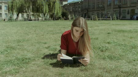 keménytáblás : Beautiful smart long brown hair girl reading a book while lying on campus green lawn. Charming intelligent young woman enjoying leisure reading interesting book on park lawn. Low angle view.