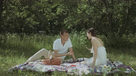 propor : Romantic man proposing to his surprised beautiful girlfriend while sitting on blanket in public park during picnic. Man giving engagement ring to excited woman while making marriage proposal outdoors.