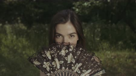 teasing : Portrait of beautiful brunette woman with deep brown eyes covering her face with hand fan over natural landscape background. Mystery woman with hand fan posing and looking at camera in summer park.