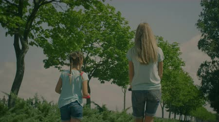 восемь : Rear view of lovely elementary age girl with pigtails and long blonde hair mother on scooters enjoying leisure while relaxing in summer park over beautiful natural landscape background. Slow motion.