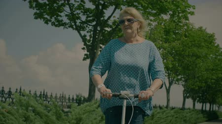 robogó : Joyful elderly in sunglasses enjoying her scooter ride while spending free time in summer park over beautiful natural landscape background. Active senior blonde woman riding kick scooter on sunny day.