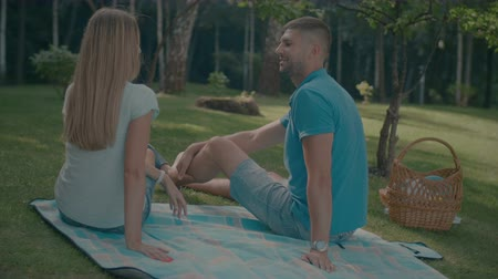 romantik : Rear view of carefree attractive couple in love sitting on checkered pinic basket and talking while spending weekend together in park. Joyful relaxed couple chatting and enjoying nature during picnic. Stok Video