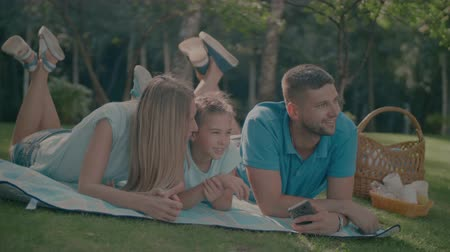 lánya : Cheerful family with adorable preteen daughter lying on picnic blanket and talking while spending great time together in nature on summer day. Joyful smiling family enjoying leisure outdoors in park.