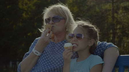 creams : Relaxed adorable preteen granddaughter and beautiful elegant grandmother in sunglasses eating tasty ice creams while enjoying leisure together on the bench in summer park. Slow motion. Stock Footage