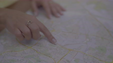 atlasz : Closeup of female hands pointing on travel map places to visit. Tourist woman planning summer vacation journey and poitining on travel map with finger travel destination. Slow motion. Stock mozgókép