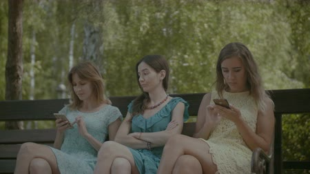 ignoring : Angry woman being ignored by her female friends networking with their smart phones while sitting on the bench in park. Unhappy beautiful girl annoyed by two girlfriends playing with cellphones.