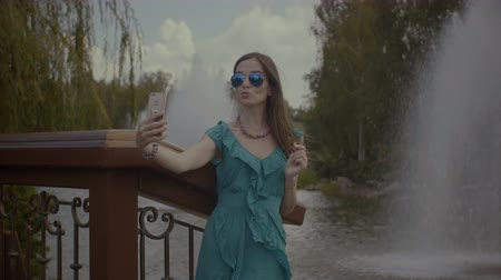 изображение : Relaxed attractive woman in sunglasses taking self portrait photo on cellphone while resting outdoors during weekend. Carefree female making selfie on smart phone while enjoying summer vacations.