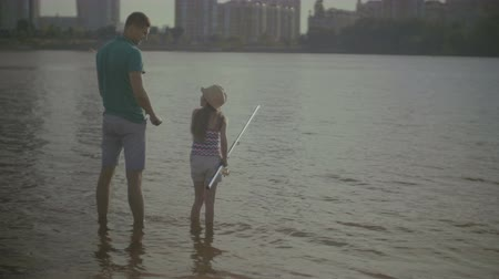 ужение : Loving handsome father and cute preteen daughter with fishing rods standing in river and angling together. Positive family spending leisure fishing together on summer day. Стоковые видеозаписи