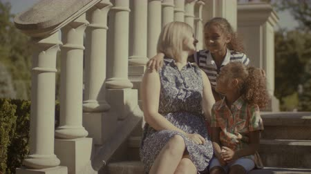 восемь : Joyful loving diverse family with two elementary age mixed race girls resting and chatting while sitting on stairs outdoors. Caucasian mother and two little sisters enjoying leisure on summer vacation