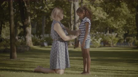 osm : Affectionate caucasian mother comforting her cute sad elementary age mixed race daughter in summer park. Caring mom encouraging her child, embracing with love and tenderness outdoors. Dostupné videozáznamy